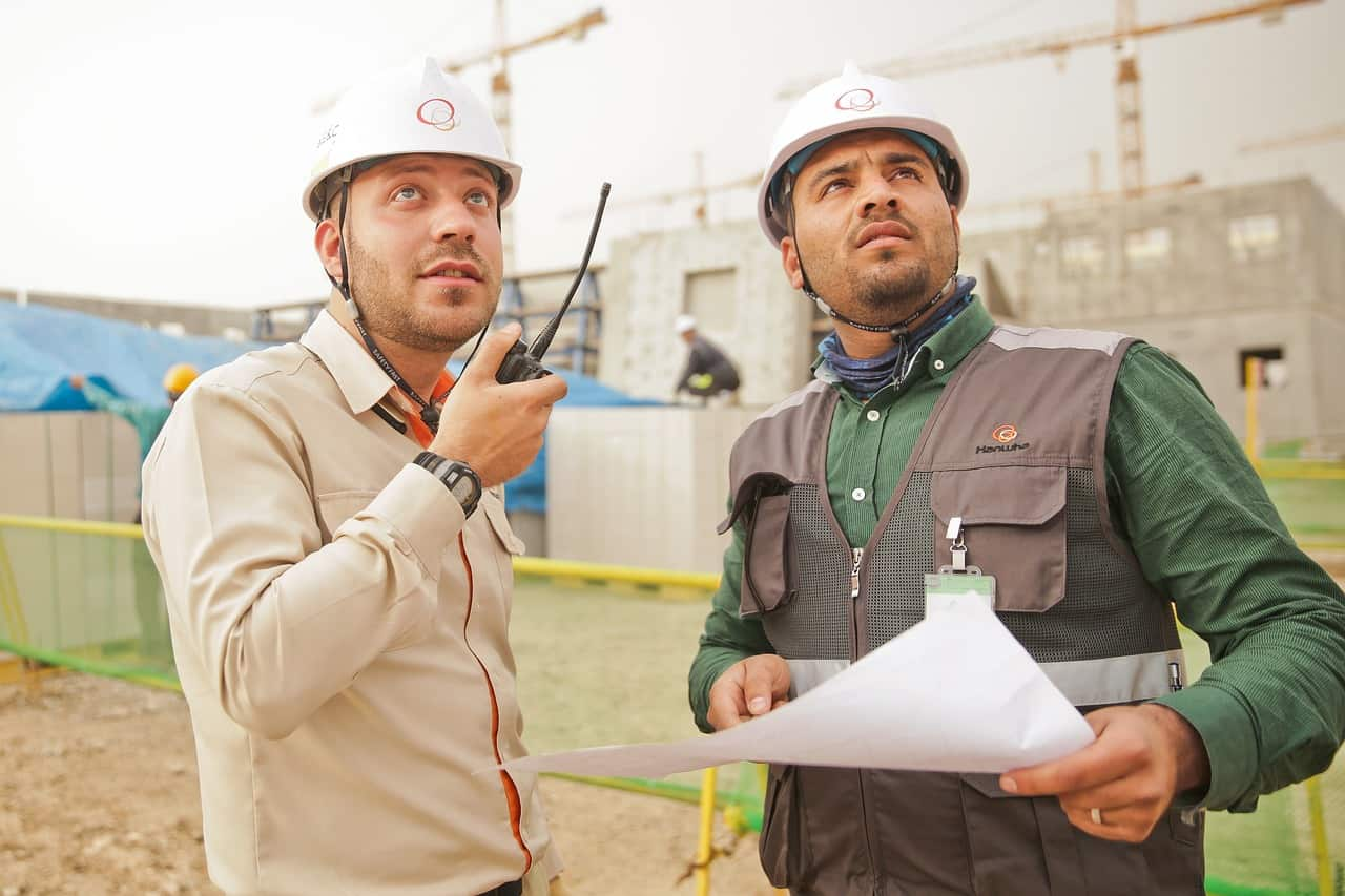 Men in construction hats talking to each other